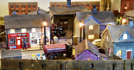 A busy N scale scene by Jules Attard, with N9 shops and N10 farmhouse. Also N28 workshop roof is just visible over the fence.\\n\\n22/12/2020 14:00